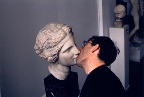 Chico besando a una escultura griega o romana