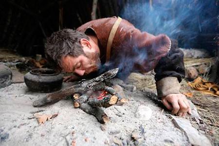 Fotograma reality 10.000 BC con hombre soplando al fuego y cerámica